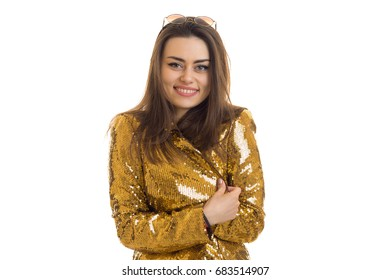 beautiful smiling Lady stands in the gold jacket and suspiciously looking at camera