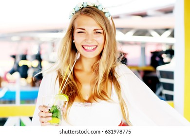 Beautiful smiling lady in white dress and flowers crown holding a glass with cocktail sitting at the summer restaurant. Outdoor shot.