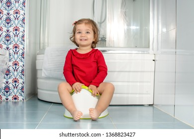 Beautiful smiling little baby sitting on potty in bathroom. Cute adorable funny child girl using chamber pot. Toilet training concept. Toddler learning to use the Toilet.