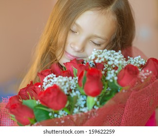 Beautiful smiling little girl with big bouquet of roses on birthday.
