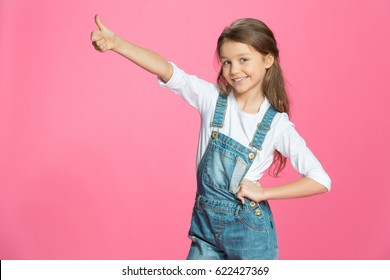 Beautiful smiling little girl in denim overalls showing thumb up on pink