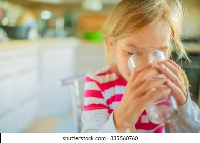 Beautiful smiling little girl drinking a glass of water against the background of the kitchen.
