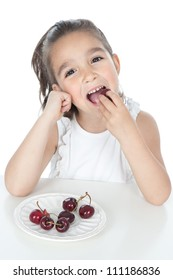 Beautiful smiling little girl eating cherries over white