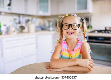 7e1c87464a3f Beautiful smiling little girl in glasses sits at a table in the kitchen.