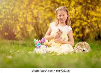 Beautiful smiling little girl holding cute bunny and sitting on the grass with Easter eggs in spring holidays. Looking at camera. Copy space.