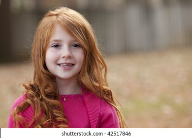 Beautiful smiling little girl with long red hair in pink sweater