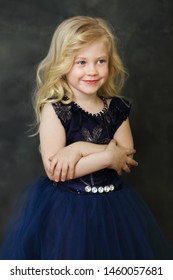 beautiful smiling little girl over dark background look outside the picture