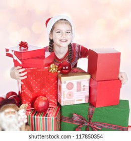 Beautiful smiling little girl in Santa's Helper hat with gifts over colorful background