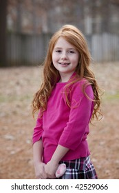 Beautiful smiling little girl with vivid red hair outdoors wearing pink sweater