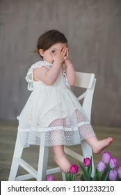 Beautiful smiling little girl in white lace dress sitting on a white chair, plays in peek-a-boo.