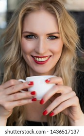 Beautiful smiling long haired blonde girl sits and rests at the table in cafe, holding a cup of coffee in her hands. Close up. Trendy, commercial design. Copy space