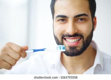 Beautiful Smiling Man Brushing Healthy White Teeth With Brush. High Resolution Image