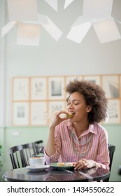 Beautiful smiling mixed race woman in pink striped dress sitting in confectionery and eating cookie.