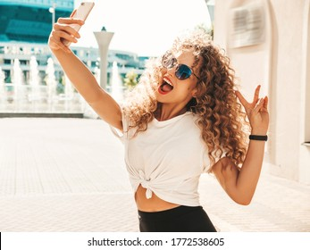 Beautiful smiling model with afro curls hairstyle dressed in summer hipster clothes.Sexy carefree girl posing in the street in sunglasses.Taking selfie self portrait photos on smartphone - Shutterstock ID 1772538605