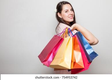 Beautiful smiling model girl holding shopping bags