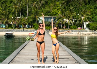 Beautiful smiling model under the palm in summer scenery,relaxing on a tropical island, makeup and hairstyle with horns, fashion,amazing tan body,sunbathing.Koh Samui, Thailand