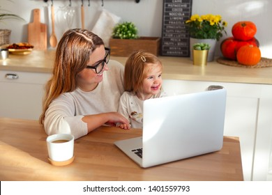 Beautiful smiling mom working at home on a laptop computer while taking care of her baby girl
