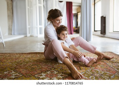 Beautiful smiling mother dressing cute little daughter spending time together on carpet at home. Family values