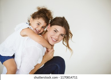 Beautiful smiling mother holding little cute daughter on back happily looking in camera together over white background. Family values