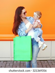 Beautiful smiling mother holding on hands baby with shopping bag, woman wearing a sunglasses and jeans clothes