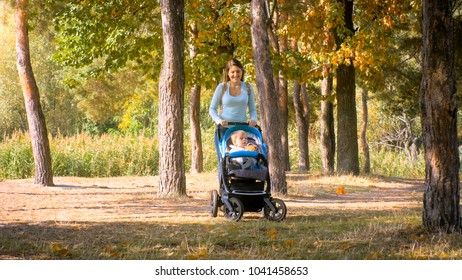 Beautiful smiling mother walking in park with toddler son sitting in pram