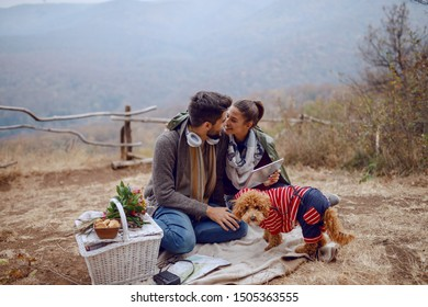 Beautiful smiling multicultural couple in love sitting on blanket at picnic in autumn and using tablet. Next to them are dog and basket with food.