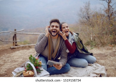 Beautiful smiling multicultural couple in love sitting on blanket at picnic in autumn, using tablet and listening music over headphones. Next to them are dog and basket with food.