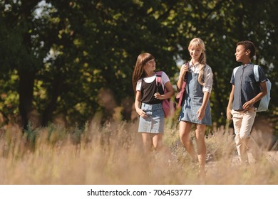 beautiful smiling multiethnic teenage friends walking together in park