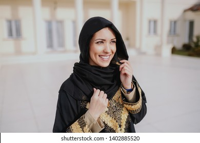 Beautiful smiling muslim woman woman posing in front of her beautiful house.