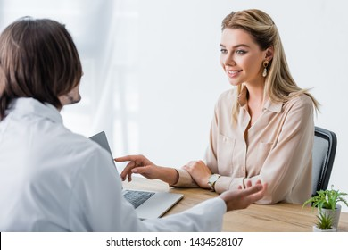 beautiful smiling patient looking at doctor and pointing with finger at laptop