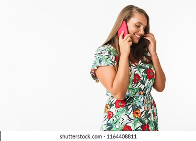 Beautiful smiling plus size girl in colorful dress happily talking on cellphone over white background