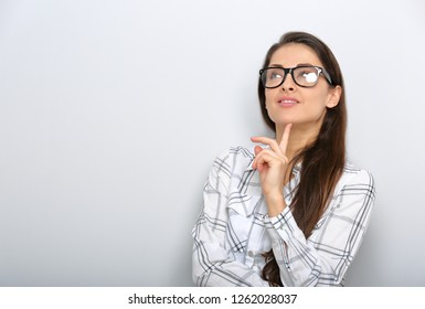 Beautiful smiling positive successful business woman in glasses looking up with confident emotion and finger under the face in white shirt and long hair.
