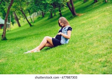 A beautiful smiling pregnant woman in a black tight dress and blue jeans jacket sitting on green grass in park and touching her belly with love and care. Walking in the park.