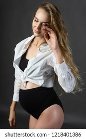 A beautiful smiling pregnant young blonde woman wearing a black maternity underwear and a white unbuttoned shirt, tied on her stomach, touches her face with her hand. Health, fashion. Copy space.
