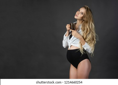 A beautiful smiling pregnant young female blonde wearing a black maternity underwear and a white unbuttoned shirt, tied on her stomach, holds a cup of hot drink in her hands. Copy space. Horizontal.