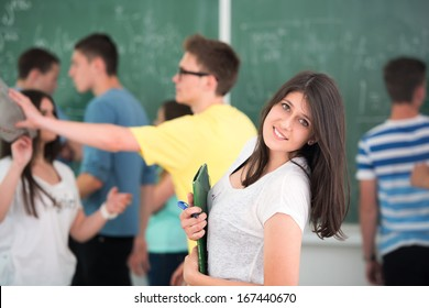 Beautiful smiling schoolgirl posing in classroom