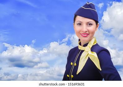 Beautiful smiling stewardess on a background sky