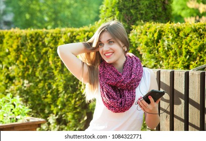 Beautiful smiling student girl listen to music on her mobile phone sitting in a summer park