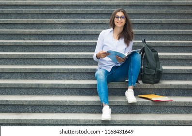 Beautiful smiling student girl with textbooks, folders, near college. A young Indian woman in glasses sits on the steps and reads books.