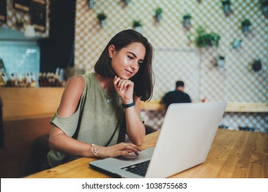 Beautiful smiling student girl using modern laptop while having lunch at coffee shop, attractive woman working via portable computer at cozy cafe bar, female freelancer searching new ideas in internet