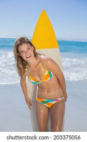 Beautiful smiling surfer girl standing on the beach with her surfboard on a sunny day