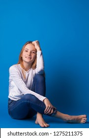 Beautiful smiling teen girl in jeans and a white blouse on blue background.