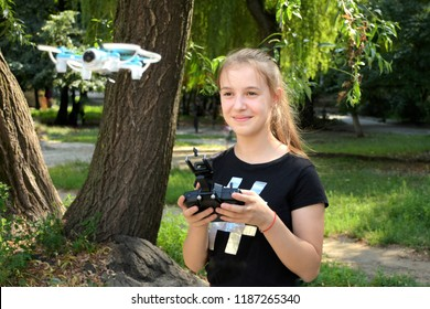 Beautiful smiling teen girl using dron. Blurred flying copter on front