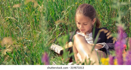Beautiful smiling teenage girl in blue blouse lying on grass and read book