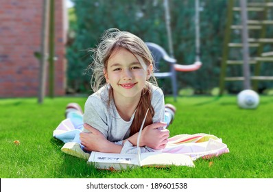 Beautiful smiling teenage girl  lying on grass and read book in summer park.