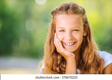 Beautiful smiling teenage girl in white blouse, against green of summer park.
