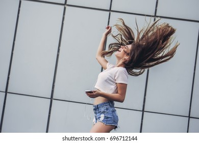 Beautiful smiling teenager with hair flying is having fun outdoors on a gray background. Young woman in earphones with mobile phone in hand is listening to music, smiling and singing.