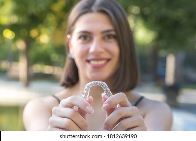 Beautiful smiling Turkish woman is holding an invisalign bracer