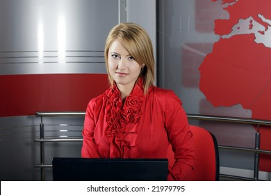beautiful smiling TV Presenter in front of the laptop and looking at the camera