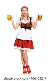 beautiful smiling waitress in traditional german costume holding beer glasses on Oktoberfest, isolated on white